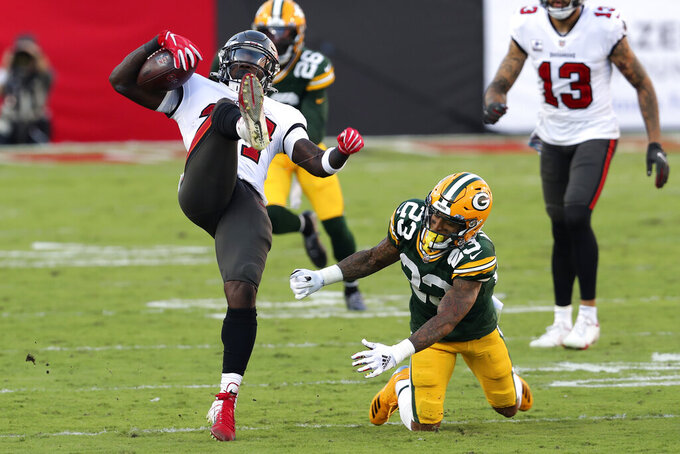 Green Bay Packers cornerback Jaire Alexander (23) trips up Tampa Bay Buccaneers running back Ronald Jones II (27) during the first half of an NFL football game Sunday, Oct. 18, 2020, in Tampa, Fla. (AP Photo/Mark LoMoglio)
