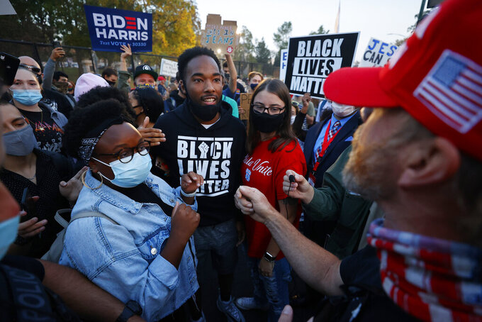 FILE - In this Oct. 7, 2020, file photo, supporters for former Vice President Joe Biden and Black Lives Matter, clash with President Donald Trump supporters prior to the vice presidential debate in Salt Lake City. Several years since its founding, BLM has evolved well beyond the initial aspirations of its early supporters. Now, its influence faces a test, as voters in the Tuesday, Nov. 3 general election choose or reject candidates who endorsed or denounced the BLM movement amid a national reckoning on race. (AP Photo/Jeff Swinger)