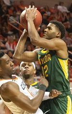 Baylor forward Flo Thamba, back, watches as Baylor guard Jared Butler, right, takes a shot over Oklahoma State forward Cameron McGriff (12) during the second half of an NCAA college basketball game in Stillwater, Okla., Saturday, Jan. 18, 2020. (AP Photo/Brody Schmidt)