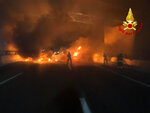 In this photo released by the Italian Firefighters, firemen try to extinguish a dozen vehicles on fire on a highway near Milan, Italy, in the early hours of Wednesday, Jan. 29. 2020. In a bid to rob an armored vehicle, a gang of thieves set up barriers of burning vehicles and spilled nails on a highway near Milan but were foiled when the driver evaded their traps. (Italian Firefighters via AP)