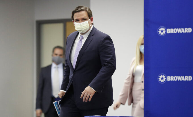 "Florida Gov. Ron DeSantis arrives at a news conference, Monday, Aug. 3, 2020, at the Broward Health Corporate Office in Fort Lauderdale, Fla. On Friday, the governor's office released a video promoting ""One Goal One Florida,"" a public service campaign that also urges Floridians to keep their distance and wear masks as a way to lower the risk of coronavirus infections. (AP Photo/Wilfredo Lee)"