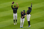 ADDS NAMES - From left to right, Miami Marlins left fielder Magnerius Sierra, right fielder Matt Joyce and center fielder Lewis Brinson celebrate after they shut out the New York Yankees in a baseball game Sunday, Sept. 27, 2020, at Yankee Stadium in New York. (AP Photo/Kathy Willens)