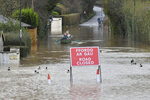 Nearby residents make their way through floodwater by boat in Monmouth, Wales, Tuesday Feb. 18, 2020. Britain's Environment Agency issued severe flood warnings Monday, advising of life-threatening danger after Storm Dennis dumped weeks' worth of rain in some places. (Ben Birchall/PA via AP)