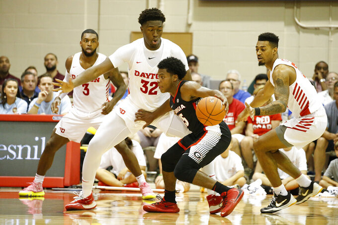 Georgia guard Sahvir Wheeler (15) tries to find his way past Dayton guard Trey Landers (3), center Jordy Tshimanga (32), and guard Ibi Watson, right, during the first half of an NCAA college basketball game Monday, Nov. 25, 2019, in Lahaina, Hawaii. (AP Photo/Marco Garcia)