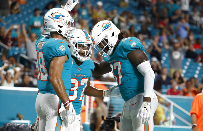 Miami Dolphins running back Myles Gaskin (37) is congratulated by wide receiver Reece Horn and tight end Clive Walford, right, after scoring a touchdown during the second half of the team's preseason NFL football game against the Atlanta Falcons, Thursday, Aug. 8, 2019, in Miami Gardens, Fla. (AP Photo/Brynn Anderson)