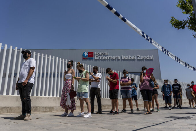People queue to be vaccinated against COVID-19 at the Isabel Zendal Hospital in Madrid, Spain, Tuesday, July 20, 2021. Spain is trying to stamp out a new wave of COVID-19 among its youth thanks to a robust vaccination program that is widely supported. Spain like the rest of the European Union got off to a slow start to compared to the United States and Britain when the first vaccines were released. But it has quickly made up ground once deliveries by drug makers started flowing. (AP Photo/Olmo Calvo)