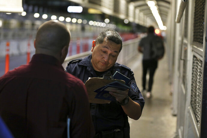 FILE - In this Sept. 17, 2019 file photo A U.S. Customs and Border Protection officer checks the documents of migrants who are on their way to apply for asylum in the United States, on International Bridge 1 as they depart Nuevo Laredo, Mexico.  The Trump administration has proposed to make it tougher for asylum-seekers to obtain permission to work in the United States while their immigration cases are pending. U.S. Citizenship and Immigration Services said Wednesday, Nov. 13, 2019  that a proposed rule would double the time asylum-seekers must wait for a work permit to a year and bar those who crossed a border illegally from applying for the permits at all. (AP Photo/Fernando Llano,File)