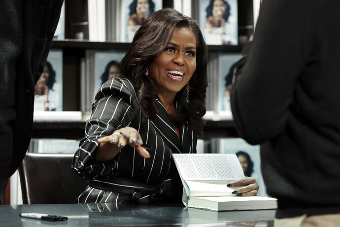 FILE - This Nov. 30, 2018 file photo shows former first lady Michelle Obama signing books during an appearance for her book,