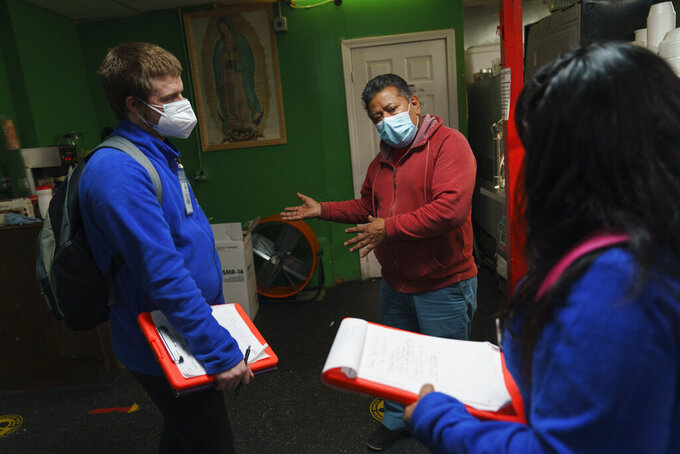 Pedro Diaz, center, talks with health ambassadors Kyle Cornell, left, and Maria Matos in a restaurant as they walk through the neighborhood trying to register residents for the COVID-19 vaccine in Central Falls, R.I., Wednesday, Feb. 24, 2021. The city has endured repeated waves of coronavirus illness, with rates of confirmed cases that often dwarfed cities across New England. (AP Photo/David Goldman)