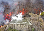 FILE - In this Monday Sept. 20, 2021 file photo, hot lava reaches a balsa normally used for for irrigation after an eruption of a volcano on the island of La Palma in the Canaries, Spain. A long-dormant volcano on a small Spanish island in the Atlantic Ocean erupted on Sunday Sept. 19, 2021, forcing the evacuation of thousands of people. Huge plumes of black-and-white smoke shot out from a volcanic ridge where scientists had been monitoring the accumulation of molten lava below the surface. (Europa Press via AP, File)