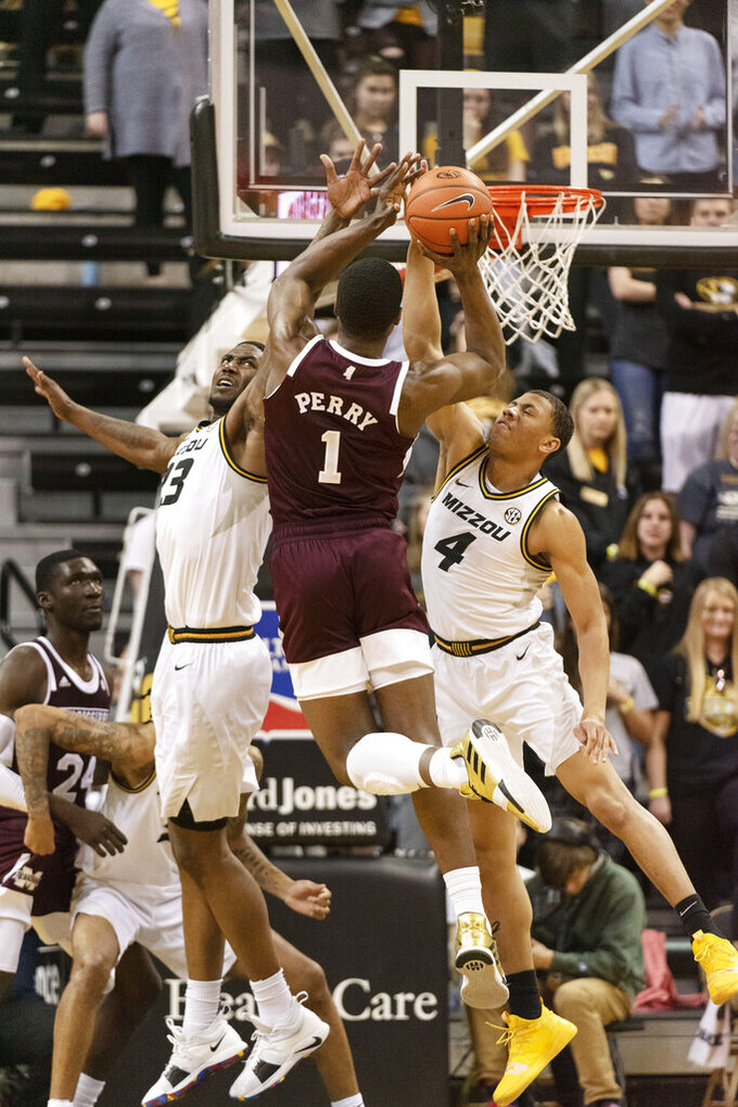 Mississippi State's Reggie Perry, center, shoots over Missouri's Javon Pickett, right, and Jeremiah Tilmon, left, during the second half of an NCAA college basketball game Saturday, Feb. 29, 2020, in Columbia, Mo. Mississippi State won 67-63. (AP Photo/L.G. Patterson)