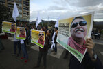 Supporters of the FARC political party holding posters of former leader Seuxis Hernandez, known by his war alias Jesus Santrich, rally outside the Attorney General's office in Bogota, Colombia, Wednesday May 15, 2019. Attorney General Nestor Martinez resigned after a special court charged with prosecuting war crimes during the country's civil conflict ruled that the former rebel leader should not be extradited to the United States on a drug warrant and should be freed from jail. (AP Photo/Fernando Vergara)