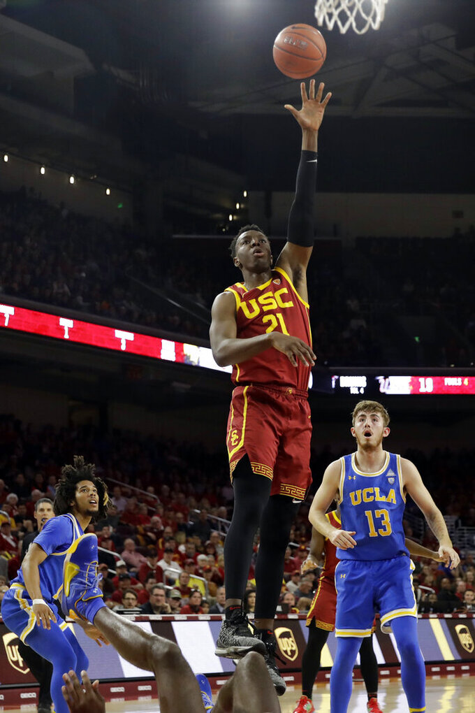 Southern California 's Onyeka Okongwu (21) shoots over UCLA guard Jake Kyman (13) and Tyger Campbell, left, during the first half of an NCAA college basketball game Saturday, March 7, 2020, in Los Angeles. (AP Photo/Marcio Jose Sanchez)