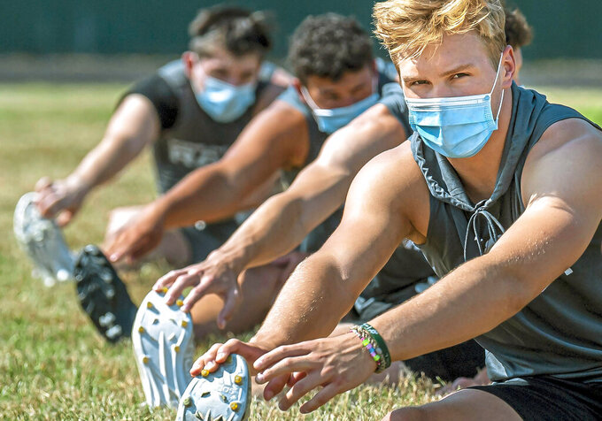 FILE — In this file photo from July 6, 2020, Pine-Richland High School quarterback Cole Spencer, right, and teammates stretch during their first practice of the season, at Richland Elementary in Pine-Richland Township near Warrendale, Pa. The Pennsylvania Interscholastic Athletic Association (PIAA) governing body for Pennsylvania interscholastic sports signaled again Monday, Aug. 17, 2020, that it's seriously considering moving ahead with the fall season despite the governor's recommendation that all youth athletics be canceled until 2021. (Steph Chambers/Pittsburgh Post-Gazette via AP, File)