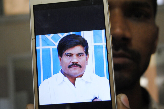 An employee of a local television channel shows a picture of slain journalist Aziz Memon on his mobile, after a demonstration to condemn his killing, in Hyderabad, Pakistan, Monday, Feb. 17, 2020. The body of Memon was found dumped in a canal just hours after he went missing while on his way to work, police said Monday. His family said he was brutally killed but that they have no idea who was behind the slaying. (AP Photo/Pervez Masih)
