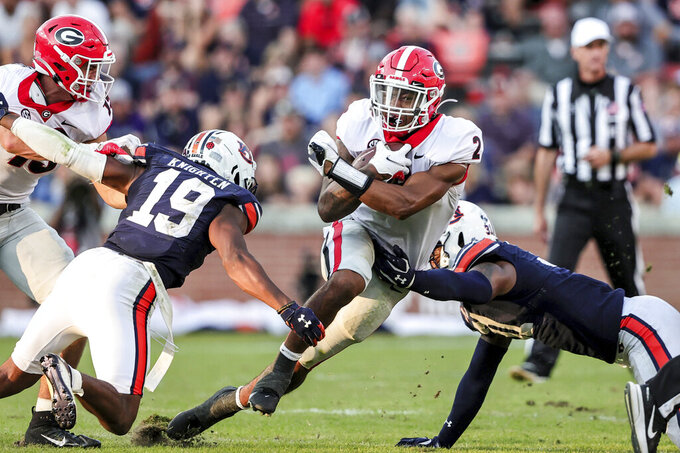 Georgia running back Kendall Milton (2) carries the ball as he splits Auburn safety Bydarrius Knighten (19) and linebacker Chandler Wooten (31) during the second half of an NCAA college football game Saturday, Oct. 9, 2021, in Auburn, Ala. (AP Photo/Butch Dill)