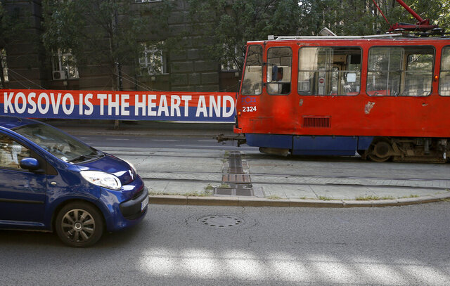 A tram car passes by a billboard reading: ''Kosovo is the heart and soul of Serbia'' placed on a street in front of the government building in Belgrade, Serbia, Wednesday, Sept. 2, 2020. Serbian President Aleksandar Vucic and Kosovo Prime Minister Avdullah Hoti will meet at the White House on Thursday and Friday. (AP Photo/Darko Vojinovic)