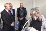 Yavuz Selim Demirag, a Turkish journalist critical of President Recep Tayyip Erdogan's government and its nationalist allies, speaks to visiting Kemal Kilicdaroglu, the leader of Turkey's main opposition Republican People's Party, left, as he rests in a hospital bed in Ankara, Turkey, Saturday, May 11, 2019. Yenicag newspaper says Saturday columnist Demirag was beaten by a group of about five or six people with baseball bats outside his home after appearing on a TV show late Friday.(AP Photo/Burhan Ozbilici)