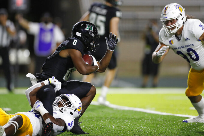 Hawaii running back Dae Dae Hunter (0) gets pulled down by San Jose State linebacker Jordan Cobbs (44) during the first half of an NCAA college football game, Saturday, Sept. 18, 2021, in Honolulu. (AP Photo/Marco Garcia)