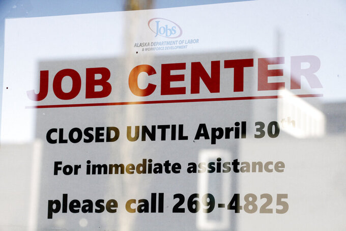 In this March 30, 2020 photo, a sign saying that the Jobs Center at the Alaska Department of Labor and Workforce Development office in midtown Anchorage, Alaska, is closed through the end of April is shown. About half of all working Americans say they or a member of their household have lost some kind of income due to the coronavirus pandemic, with low-income Americans and those without college degrees especially likely to have lost a job. That's according to a new poll from The Associated Press-NORC Center for Public Affairs Research.  (AP Photo/Mark Thiessen)
