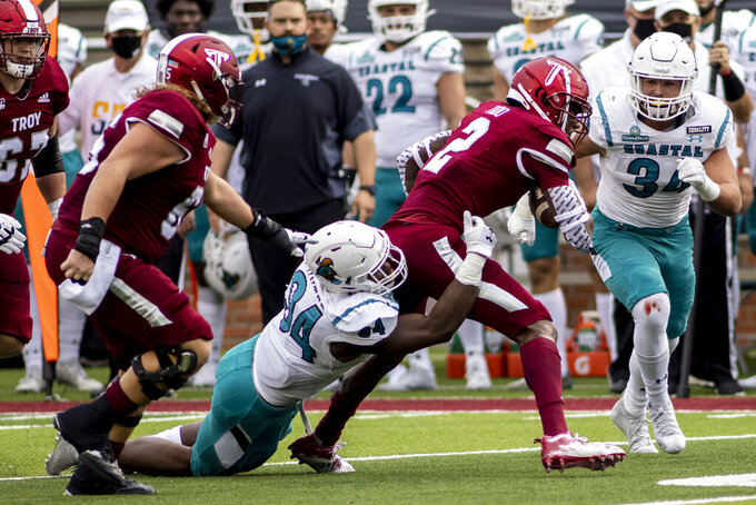 Troy wide receiver Reggie Todd (2) battles Coastal Carolina linebacker Jeffrey Gunter (94) on a run during the first half of an NCAA college football game, Saturday, Dec. 12, 2020, in Troy, Ala. (AP Photo/Vasha Hunt)