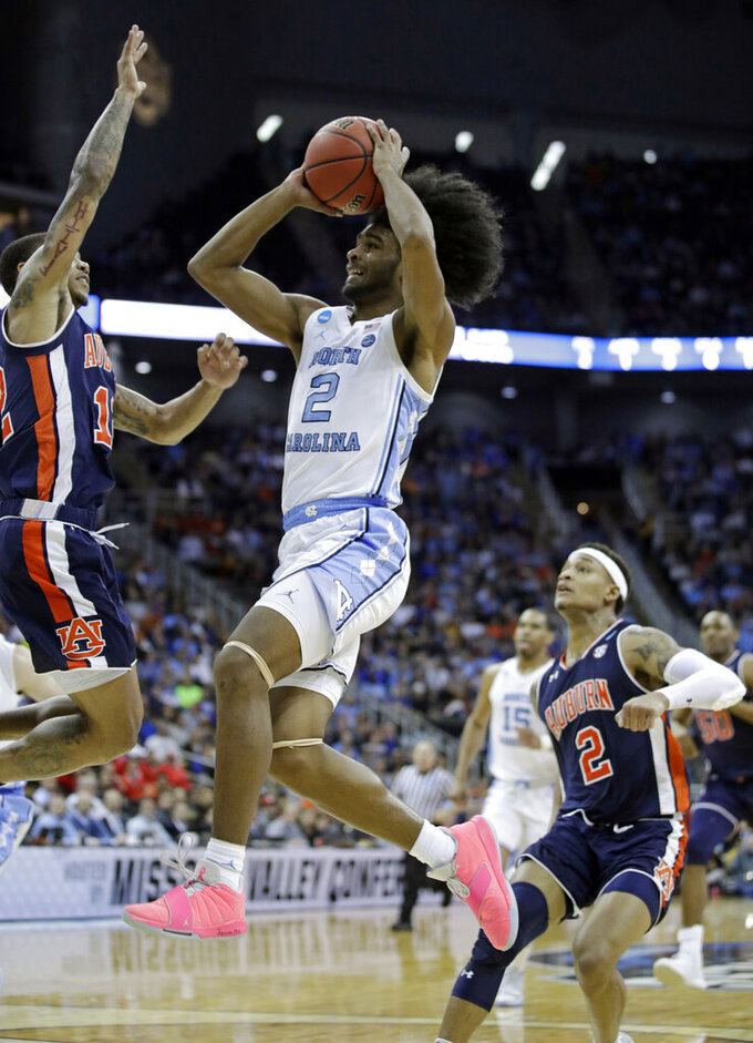 North Carolina's Coby White (2) heads to the basket as Auburn's J'Von McCormick, left, and Bryce Brown (2) defend during the first half of a men's NCAA tournament college basketball Midwest Regional semifinal game Friday, March 29, 2019, in Kansas City, Mo. (AP Photo/Charlie Riedel)