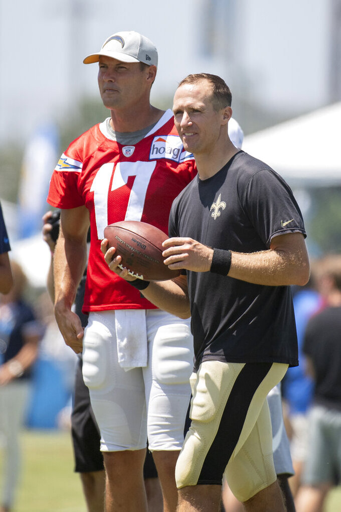 Los Angeles Chargers quarterback Philip Rivers, left, and New Orleans Saints quarterback Drew Brees look on during a joint NFL football  practice in Costa Mesa, Calif., Thursday, Aug. 15, 2019. (AP Photo/Kyusung Gong)
