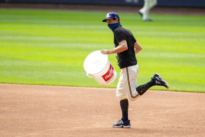Milwaukee Brewers manager Craig Counsell runs with a bucket after it was announced that the Brewers home opener was postponed after two St. Louis Cardinals employees tested positive for the coronavirus, Friday, July 31, 2020, in Milwaukee. (AP Photo/Morry Gash)