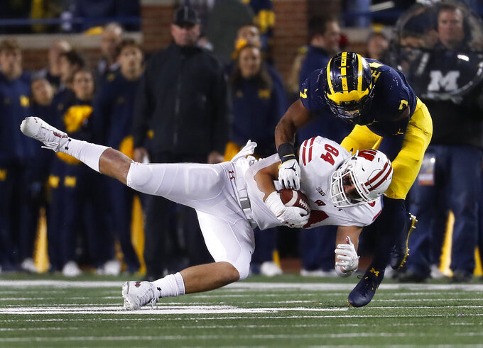 Wisconsin tight end Jake Ferguson (84) is brought down, after a reception, by Michigan linebacker Khaleke Hudson (7) during the second half of an NCAA college football game in Ann Arbor, Mich., Saturday, Oct. 13, 2018. (AP Photo/Paul Sancya)