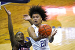 Washington's RaeQuan Battle (21) shoots over Arizona's Bennedict Mathurin during the first half of an NCAA college basketball game Thursday, Dec. 31, 2020, in Seattle. (AP Photo/Elaine Thompson)