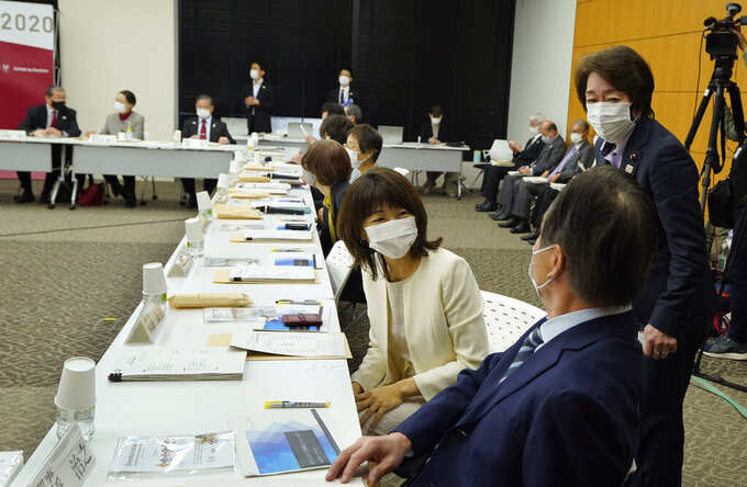 Seiko Hashimoto, right, President of the Tokyo 2020 Organizing Committee of the Olympic and Paralympic Games, talks with newly appointed executive board member Naoko Takahashi, center, gold medalist of Sydney Olympic Games women's marathon, before Hashimoto delivers her opening remarks of the executive board meeting in Tokyo, Japan, Monday, March 22, 2021. The 12 new executive board members, who were appointed on March 3, made speech at the meeting. (Kimimasa Mayama/Pool Photo via AP)