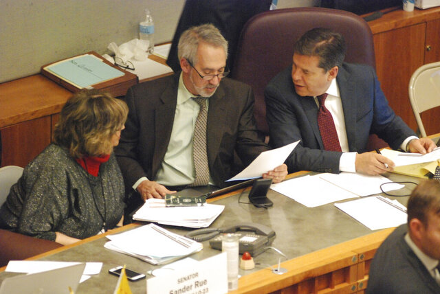 Three sponsors of red flag gun legislation confer during a floor debate at the New Mexico state Senate on Friday, Feb. 7, 2020. They are Sen. Joseph Cervantes, D-Las Cruces, right, and Reps. Daymon Ely, center, D-Corrales, and Joy Garratt, left, D-Albuquerque. The gun proposal would allow law enforcement officers to petition a state district court to order the temporary surrender of firearms by people who appear to pose a danger to themselves or others. (AP Photo/Morgan Lee)