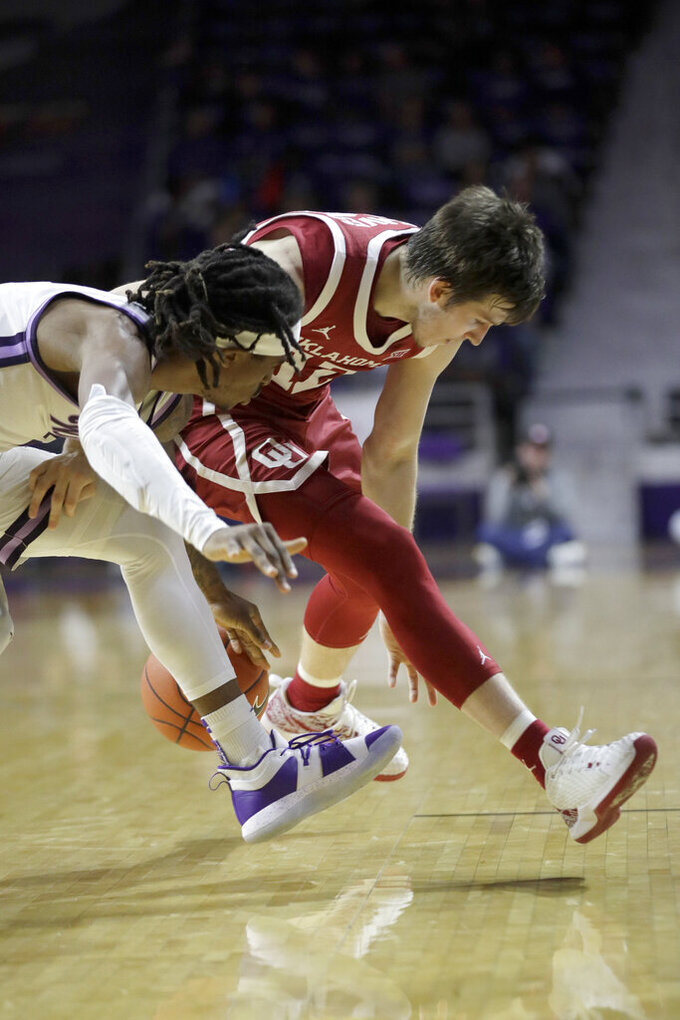 Oklahoma guard Austin Reaves (12) and Kansas State guard Cartier Diarra, left, compete for a loose ball during the second half of an NCAA college basketball game in Manhattan, Kan., Wednesday, Jan. 29, 2020. Kansas State won 61-53. (AP Photo/Orlin Wagner)
