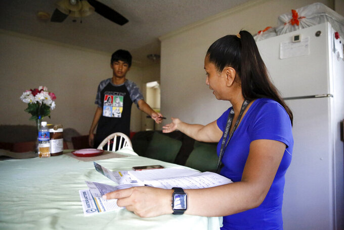Mark Daniel Taboniar hands a pen to his mother, Mary Taboniar, a housekeeper at the Hilton Hawaiian Village resort in Honolulu, as she looks over bills at her home in Waipahu, Hawaii, Saturday, Sept. 4, 2021. Taboniar went 15 months without a paycheck, thanks to the COVID pandemic. The single mother of two saw her income completely vanish as the virus devastated the hospitality industry. Taboniar is one of millions of Americans for whom Labor Day 2021 represents a perilous crossroads. (AP Photo/Caleb Jones)