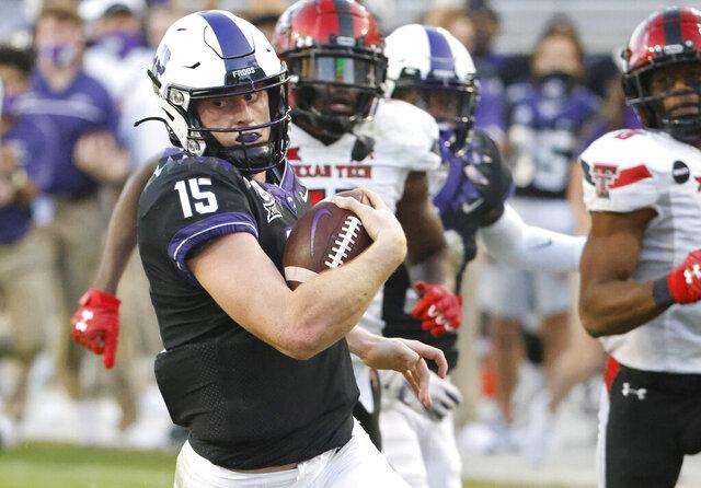 TCU quarterback Max Duggan (15) takes off past Texas Tech defensive back Eric Monroe (11) and Texas Tech defensive back Zech McPhearson (8) on a 48-yard touchdown run during the second half of an NCAA college football game Saturday, Nov. 7, 2020, in Fort Worth, Texas. TCU won 34-18. (AP Photo/Ron Jenkins)