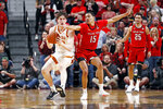 Texas Tech's Kevin McCullar (15) tries to steal the ball from Texas' Will Baker (50) during the first half of an NCAA college basketball game Saturday, Feb. 29, 2020, in Lubbock, Texas. (AP Photo/Brad Tollefson)