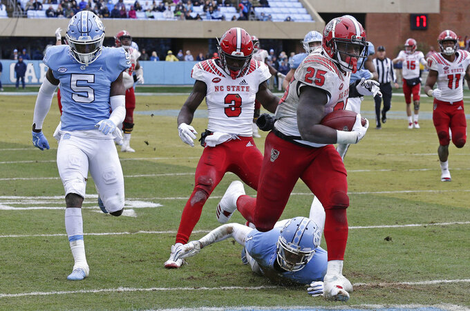 North Carolina State's Reggie Gallaspy II (25) scores a touchdown as North Carolina's Patrice Rene (5) and Myles Dorn (1) chase during the second half of an NCAA college football game in Chapel Hill, N.C., Saturday, Nov. 24, 2018. North Carolina State won 43-28 in overtime. (AP Photo/Gerry Broome)