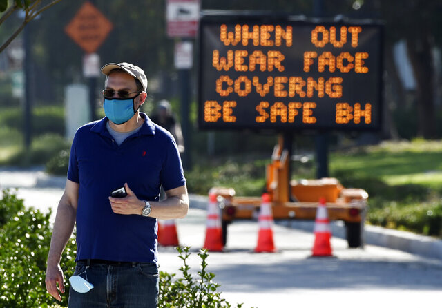 FILE - In this April 16, 2020, file photo, an electronic sign on Santa Monica Boulevard reminds people to wear masks to limit the spread of coronavirus in Beverly Hills, Calif. Gov. Gavin Newsom's administration on Thursday, June 18, 2020, mandated that Californians wear masks in most indoor settings as the state continues to battle the coronavirus. (AP Photo/Chris Pizzello, File)