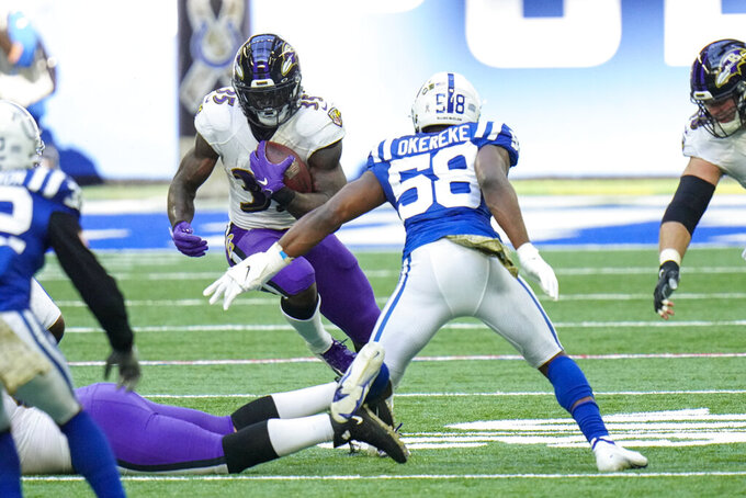 Baltimore Ravens running back Gus Edwards (35) cuts away from Indianapolis Colts inside linebacker Bobby Okereke (58) in the first half of an NFL football game in Indianapolis, Sunday, Nov. 8, 2020. (AP Photo/AJ Mast)
