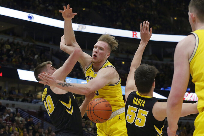Michigan's Ignas Brazdeikis is fouled by Iowa's Joe Wieskamp (10) during the first half of an NCAA college basketball game in the quarterfinals of the Big Ten Conference tournament, Friday, March 15, 2019, in Chicago. (AP Photo/Kiichiro Sato)
