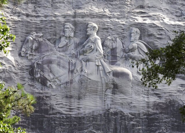 FILE - This June 23, 2015, file photo shows a carving depicting Confederate Civil War figures Stonewall Jackson, Robert E. Lee and Jefferson Davis, in Stone Mountain, Ga. An activist group has presented its plans for changes to Confederate imagery at Georgia's popular Stone Mountain Park, including a suggestion that it stop maintaining a colossal sculpture of Confederate leaders. Members of the Stone Mountain Action Coalition spoke Monday, Sept. 14, 2020, at a meeting with board members of the association responsible for the park, the Atlanta Journal-Constitution reported. (AP Photo/John Bazemore, File)