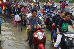Garment workers make their way to work through a flooded street following recent rains on the outskirts of Phnom Penh, Cambodia, Wednesday, Oct. 14, 2020. A Cambodian disaster official said Wednesday that more than 10,000 people have been evacuated to safety places after a tropical storm hit the country, causing the flash flood. (AP Photo/Heng Sinith)