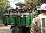 A Myanmar official stands while a truck carrying released prisoners park near the gate at Insein prison Tuesday, April 17, 2018, Yangon, Myanmar. Myanmar President Win Myint has granted amnesty to more than 8,500 prisoners, reportedly including at least three dozen political prisoners. (AP Photo/Thein Zaw)