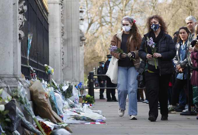 Two people carry flowers to place in front of the gate at Buckingham Palace in London, Friday, April 9, 2021. Buckingham Palace officials say Prince Philip, the husband of Queen Elizabeth II, has died. He was 99. (AP Photo/Alastair Grant)