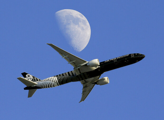 FILE - In this Aug. 23, 2015, file photo, an Air New Zealand passenger plane flies past the moon on its way to the Los Angeles International Airport from London, in Whittier, Calif. New Zealand's national carrier admitted a registration mistake turned back a flight to China over the weekend, prompting Prime Minister Jacinda Ardern to say Monday, Feb. 11, 2019,  that politics were not involved. (AP Photo/Nick Ut, File)