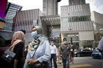 Shoppers wearing face masks to help curb the spread of the coronavirus, walk outside a shopping mall in downtown Kuala Lumpur, Malaysia, on Thursday, June 25, 2020. Malaysia began reopening schools Wednesday while entering the Recovery Movement Control Order (RMCO) after three months of coronavirus restrictions. (AP Photo/Vincent Thian)