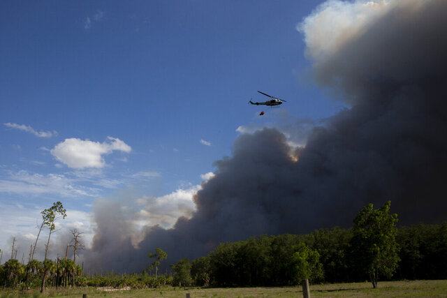 A helicopter, carrying a bucket, flies near a brush fire in Golden Gate Estates, Fla., on Wednesday, May 13, 2020. Crews worked to contain four brush fires totaling about 400 acres and threatening 30 homes in the Estates. (Jon Austria/Naples Daily News via AP)