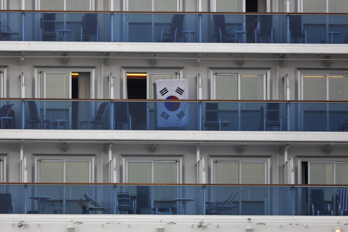 A South Korean flag hangs outside a cabin of the quarantined Diamond Princess cruise ship Saturday, Feb. 15, 2020, in Yokohama, near Tokyo. A viral outbreak that began in China has infected more than 67,000 people globally. The World Health Organization has named the illness COVID-19, referring to its origin late last year and the coronavirus that causes it. (AP Photo/Jae C. Hong)