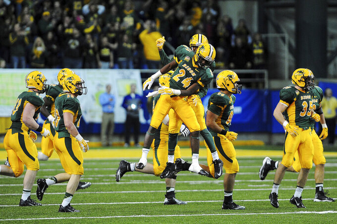 FILE - In this Dec. 6, 2014, file photo, North Dakota State's Tre Dempsey (24) and C.J. Smith (6) celebrate with teammates after a pass interception against South Dakota State during the second half of an NCAA Football Championship Subdivision playoff game in Fargo, N.D. North Dakota State's teams routinely compete for national titles in a division where that means playing 15-plus games per season. (Joe Ahlquist/The Argus Leader via AP, File)