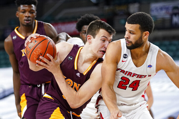 Iona's Dylan van Eyck, left, tries to get past Fairfield's Jesus Cruz in the first half of an NCAA college basketball game during the finals of the Metro Atlantic Athletic Conference tournament, Saturday, March 13, 2021, in Atlantic City, N.J. (AP Photo/Matt Slocum)